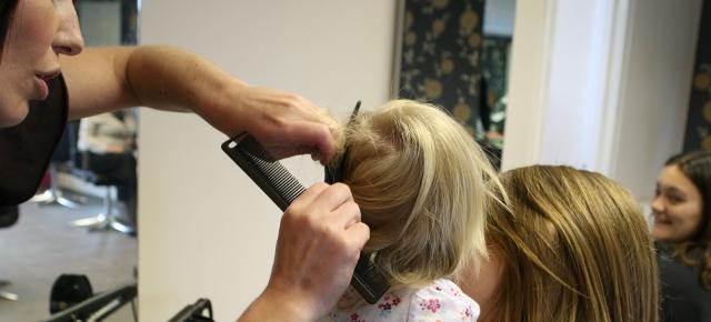 Kadeřnice stříhá vlasy v salonu malému dítěti